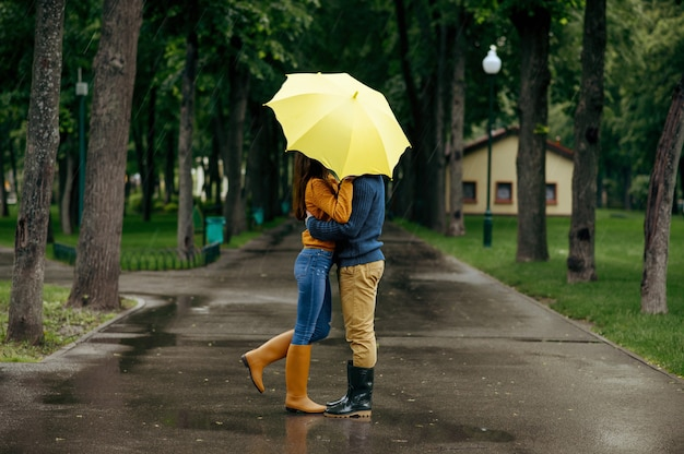 Love couple kissing in park, summer rainy day. man and woman stand under umbrella in rain, romantic date on walking path, wet weather in alley