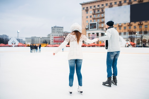 Love couple learn to skate on the rink