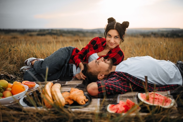 Love couple lies on plaid, fruit picnic in summer field. romantic junket of man and woman