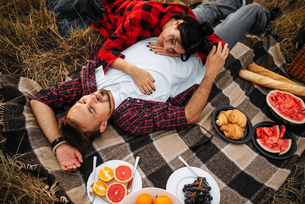 Love couple lies on plaid, picnic in summer field. romantic junket of man and woman