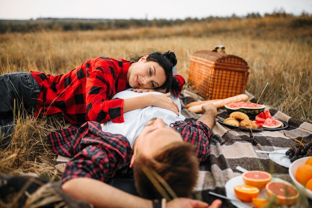 Love couple lies on plaid, picnic in summer field