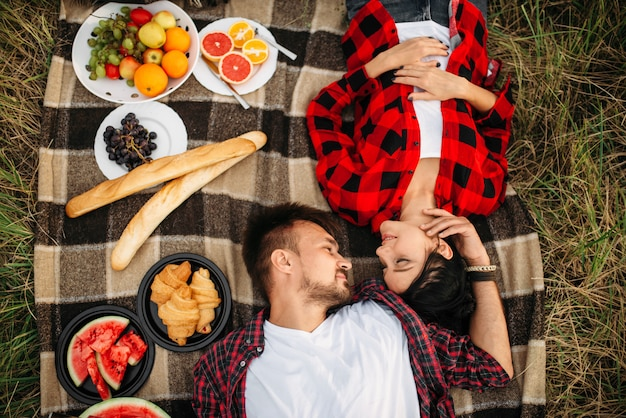 Love couple lies on plaid, top view, picnic in summer field. romantic junket of man and woman