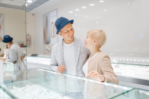 Влюбленная пара смотрит на драгоценности в ювелирном магазине