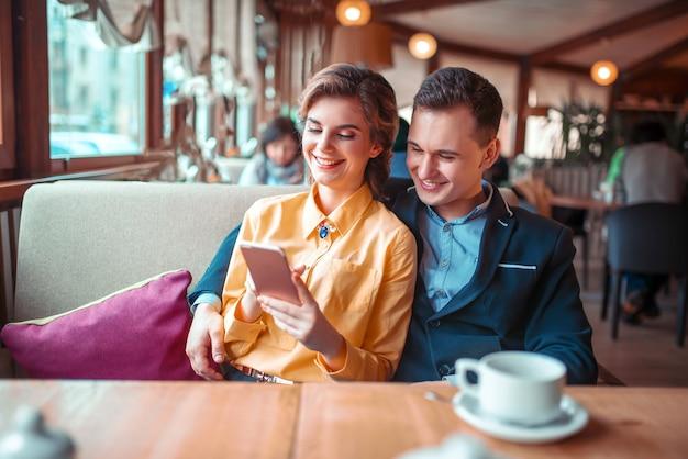 愛のカップルがレストランで電話のフォトアルバムを見る