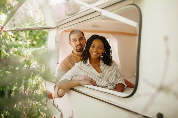 愛のカップルはトレーラーでキャンプし、rvウィンドウの外を見ています。男性と女性はバンで旅行し、キャンピングカーでロマンチックな休暇を過ごし、キャンピングカーでキャンピングカーのレジャーを楽しみます