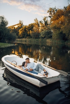 Love couple lying in a boat on quiet lake at summer day at sunset. romantic meeting, boating trip, man and woman walking along the river