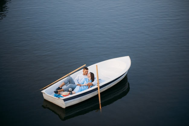 Love couple lying in a boat on silent lake, top view. romantic meeting, boating trip, man and woman walking along the lake