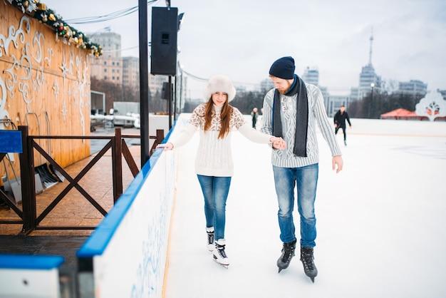 カップルが大好きで、男性は女性がスケートリンクでスケートをすることを学びます。野外での冬のスケート、アクティブなレジャー、アイススケート