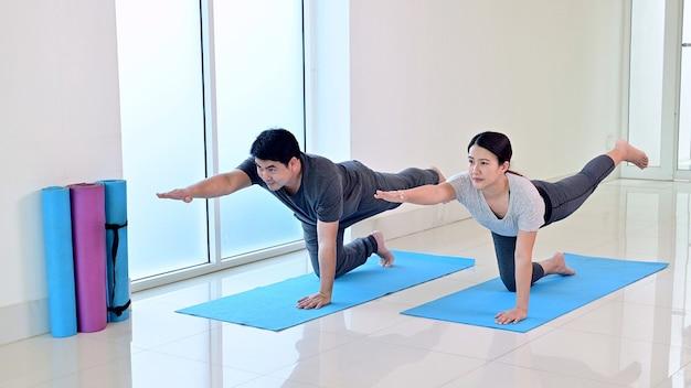 집에서 함께 요가 호흡과 명상을 배우는 온라인 커플을 사랑하세요. 건강을 위한 스포츠와 운동. 아시아 여자와 남자의 라이프 스타일입니다.