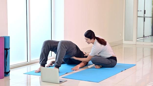 自宅で一緒にヨガの呼吸と瞑想をオンラインで学ぶカップルが大好きです。健康のためのスポーツと運動。アジアの女性と男性のライフスタイル。