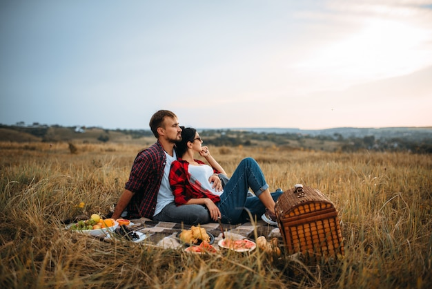 Love couple, picnic on plaid in summer field. romantic junket of man and woman