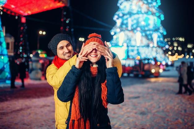 Влюбленная пара играет угадай, кто на площади