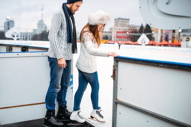 Love couple prepares to skate on the rink