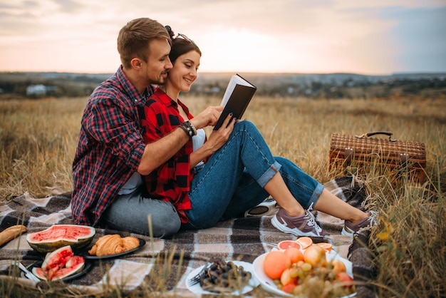 Love couple reads book together, picnic on the grass. romantic junket, man and woman on outdoor dinner,  happy family weekend