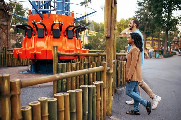 Влюбленная пара, отдыхая в парке развлечений, аттракционе. мужчина и женщина отдыхают на открытом воздухе. семейный отдых летом, развлекательная тематика