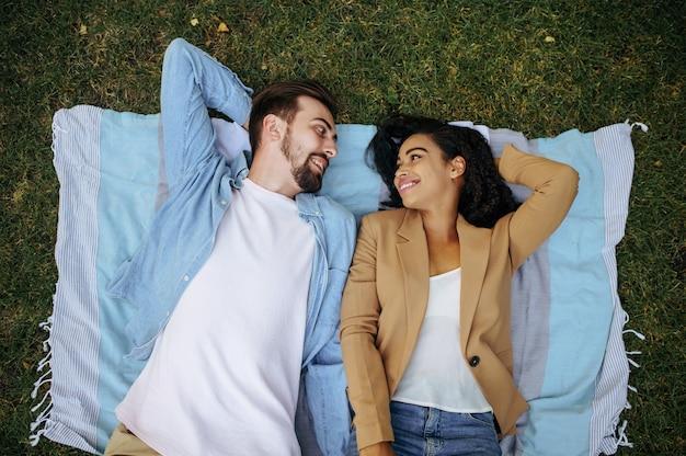 잔디, 평면도, 공원에서 산책에 쉬고 사랑 커플. 남자와 여자는 담요에 누워. 가족은 여름에는 초원에서, 주말에는 자연에서 휴식을 취합니다.
