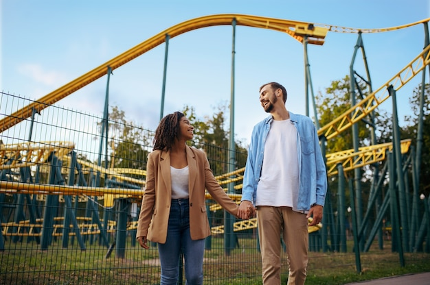 Love couple at the roller coaster in amusement park, attraction. man and woman relax outdoors. family leisures in summertime, entertainment theme
