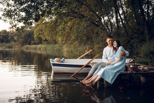 静かな湖の桟橋に座っている愛のカップル。ロマンチックな出会い、ボート旅行、川沿いをボートで歩く男女
