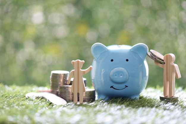 Love couple and stack of coins money with blue piggy bank on natural green background