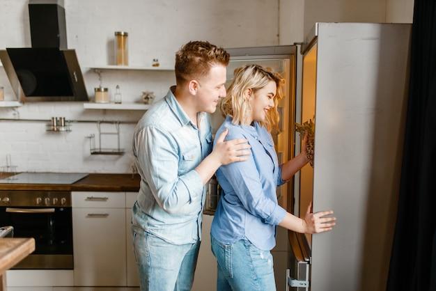 Влюбленная пара достает фрукты из холодильника, приготовление романтического ужина.