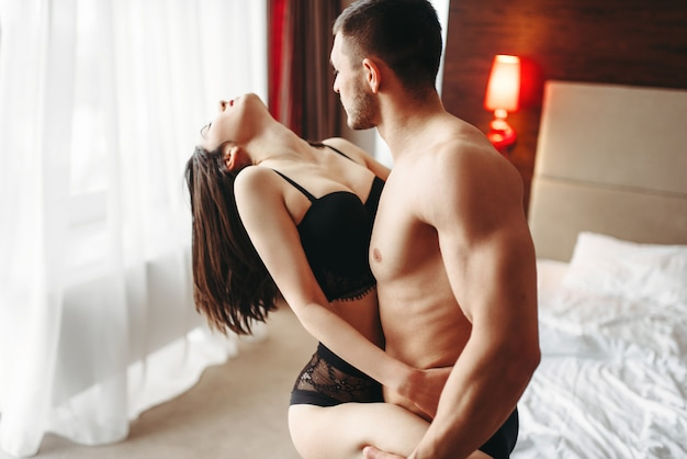 Love couple in underwear hugging in luxury bedroom