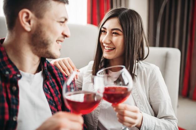愛のカップルが映画を見て、赤ワインを飲む