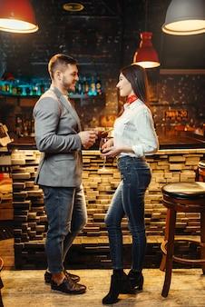 バーカウンター、ロマンチックな夜に立っているアルコール飲料とのカップルが大好きです。
