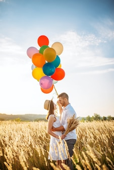 Love couple with balloons hugs in wheat field