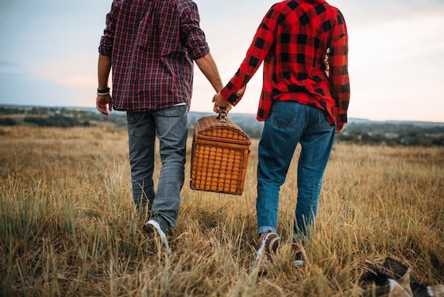 バスケットが付いているカップル、夏の畑でのピクニックが大好きです。ロマンチックなジャンケット、男性と女性のレジャー、一緒に幸せな家族の週末