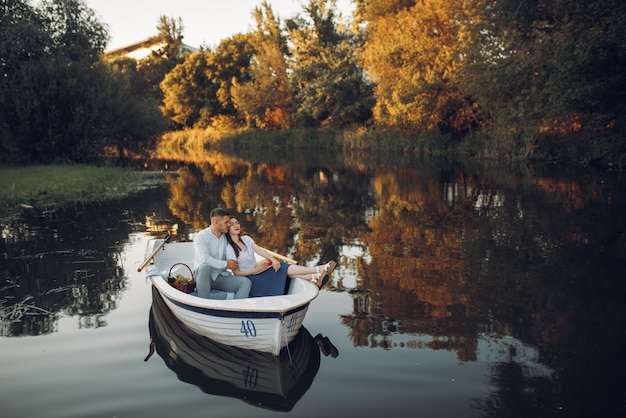 Love couple with fruit basket lying in a boat on quiet lake at summer day. romantic meeting, boating trip, man and woman walking along the river