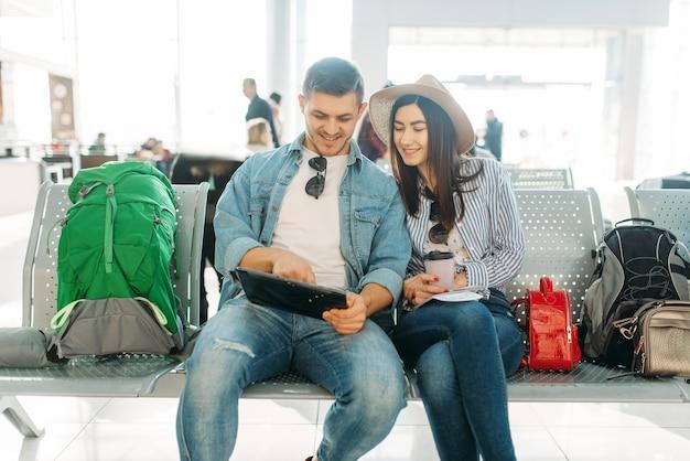 Влюбленная пара с багажом в ожидании вылета в аэропорту. пассажиры с багажом в аэровокзале