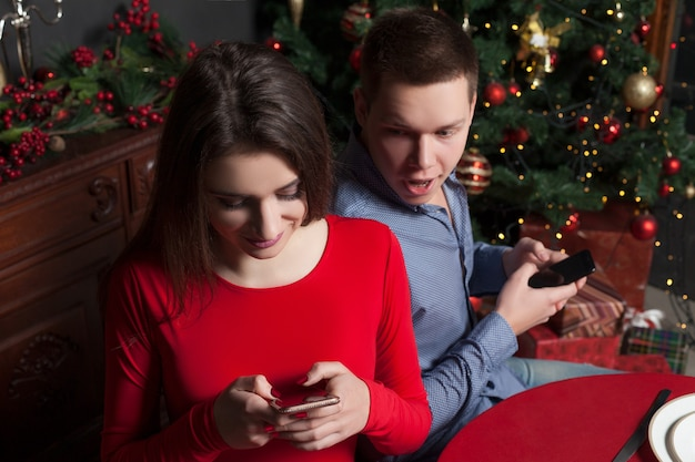 Love couple with mobile phones at luxury restaurant.