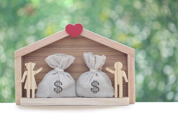 녹색 배경에 가방에 모델 하우스와 동전 돈을 사랑 커플