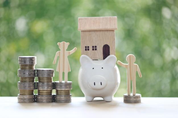 貯金箱のモデルハウスと自然な緑の背景にコインのお金のスタックとカップルを愛する
