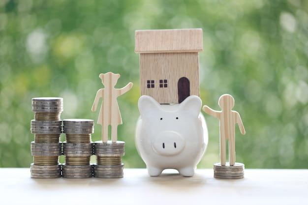 Love couple with model house on piggy bank and stack of coins money on natural green background