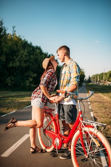 Love couple with vintage bicycle walking in summer park, romantic date of young man and woman. boyfriend and girlfriend together outdoor, retro bike
