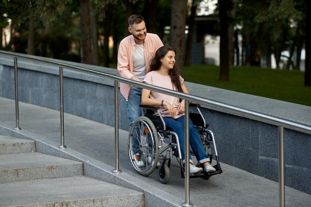 Влюбленная пара с инвалидной коляской гуляет в осеннем парке