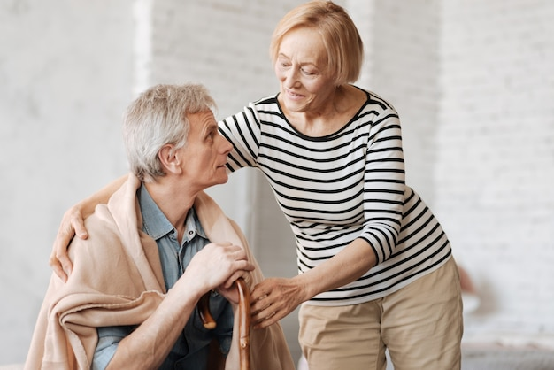 Любовь все лечит. приятная милая пожилая женщина следит за тем, чтобы ее мужчина чувствовал себя комфортно и тепло, одновременно давая ему одеяло и немного обнимая его
