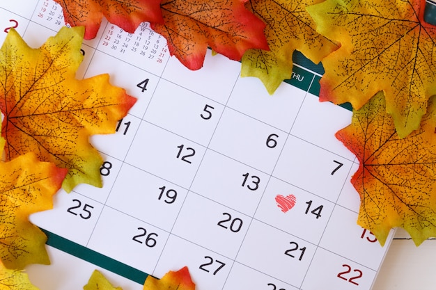 Love day concept. calendar to remain valentine's day with maple leaf background.valentine day, february14