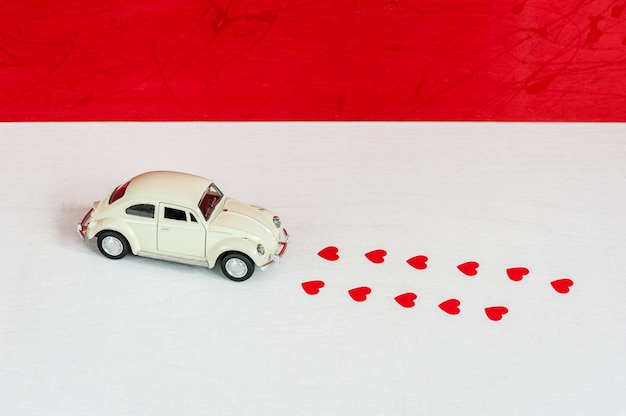 Love delivery concept. toy retro car and traces of the machine in hearts shapes