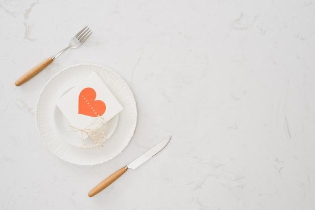 白い背景、愛とロマンスの概念のプレートに赤いリボンとフォークとスプーンのネクタイを設定する愛のディナー