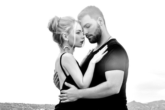 In love eastern couple in mountains of cappadocia hugs and kisses. love and emotions loving couple vacationing in turkey. closeup portrait man and woman. beautiful crescent moon earrings on girl ears