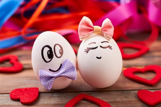 Люблю яйца и красные сердца. бантики на яйца с лицами. искусство и еда.