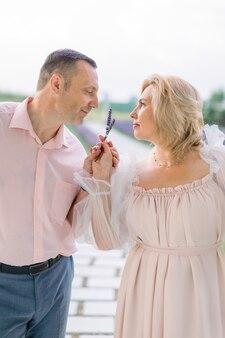 사랑, 가족 및 감정 개념입니다. 사랑에 빠진 행복한 성숙한 부부의 클로즈업, 야외에서 함께 서서 라벤더 향기 즐기기