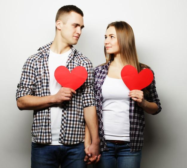 愛、家族、人々の概念:赤いハートを持って愛の幸せなカップル