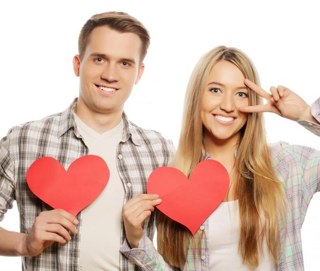 愛、家族、人々の概念:赤いハートを保持している愛の幸せなカップル