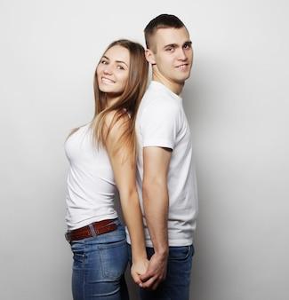 Концепция любви, семьи и людей: прекрасная счастливая пара, обнимая на сером фоне.