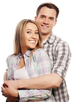 Концепция любви, семьи и людей: прекрасная счастливая пара, обнимая на белом фоне.
