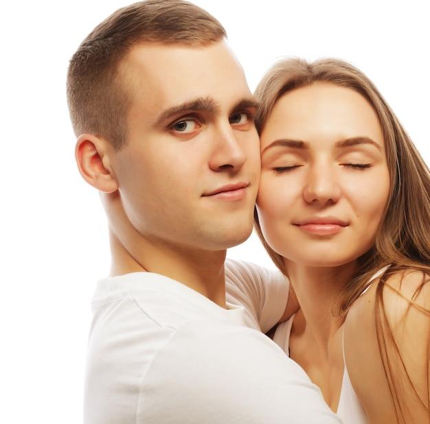 愛、家族、人々の概念:白い背景の上に抱き締める素敵な幸せなカップル。