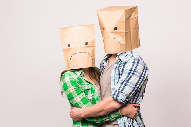사랑, 가족, 관계 문제 개념 - 불행한 커플은 슬픈 얼굴을 흰색 배경 위에 종이 가방으로 덮고 있습니다.